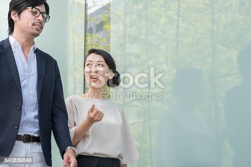 istock Japanese Businessman and Businesswoman Talking, Walking Outside Modern Office Building 540836846