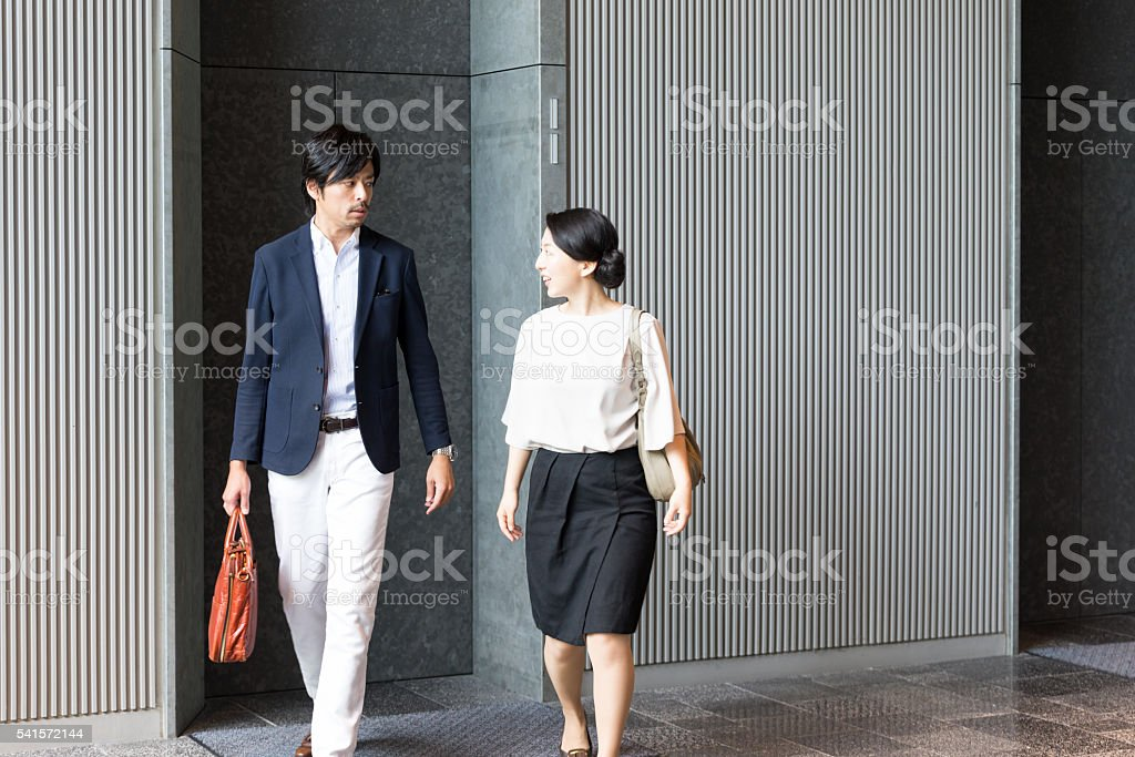people talking in elevator. japanese businessman and businesswoman walking, talking at elevator hall royalty-free stock photo people in e