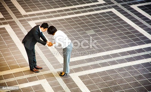 Japanese businessman bowing as he handshakes black female colleague