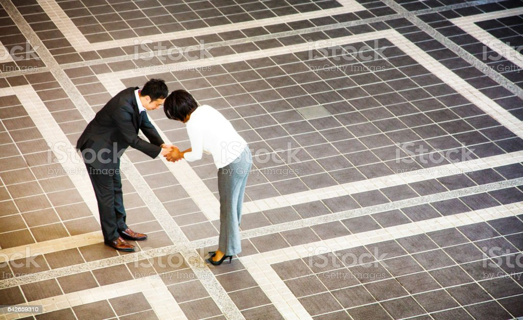 Japanese businessman bowing as he handshakes female colleague stock photo