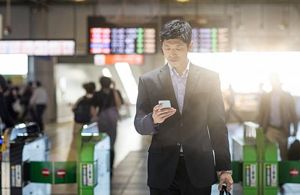 japanese businessman checking the mobile phone at the station - 駅 ストックフォトと画像