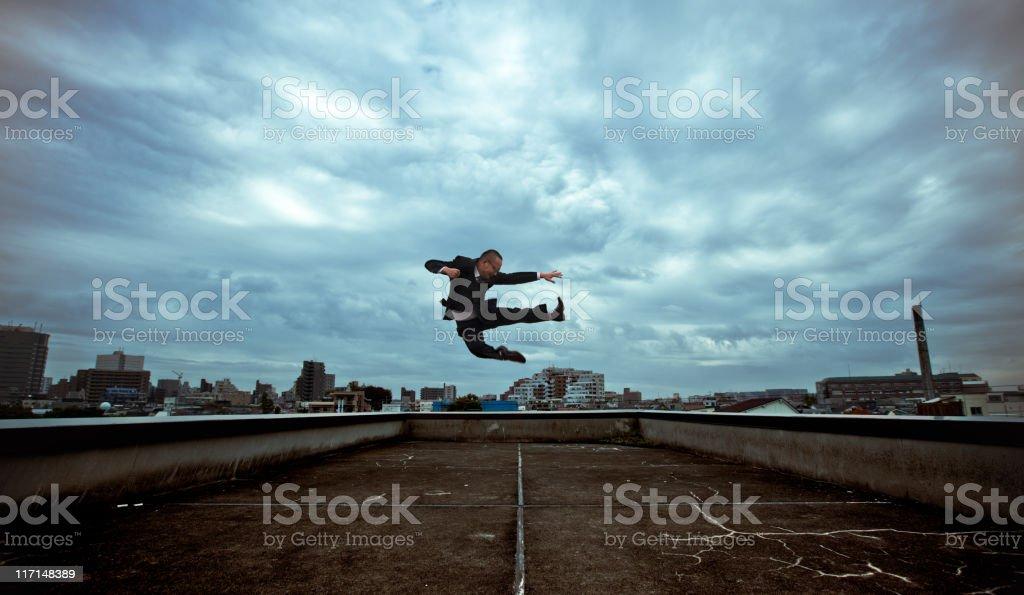 Japanese businessman doing a flying kick royalty-free stock photo