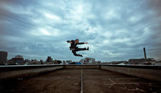 hombre de negocios japonés hace un kick aéreo - ninja fotografías e imágenes de stock