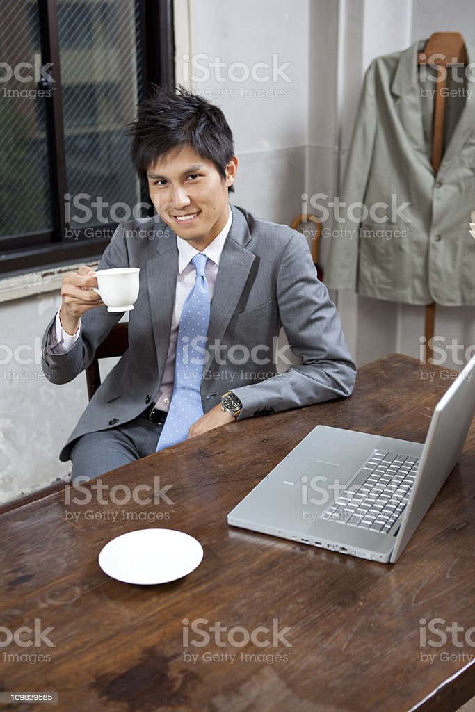 Japanese Businessman drinking coffee at desk royalty-free stock photo