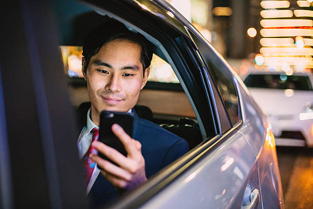 japanese businessman in a car at the night - asian travel in car stock photos and pictures