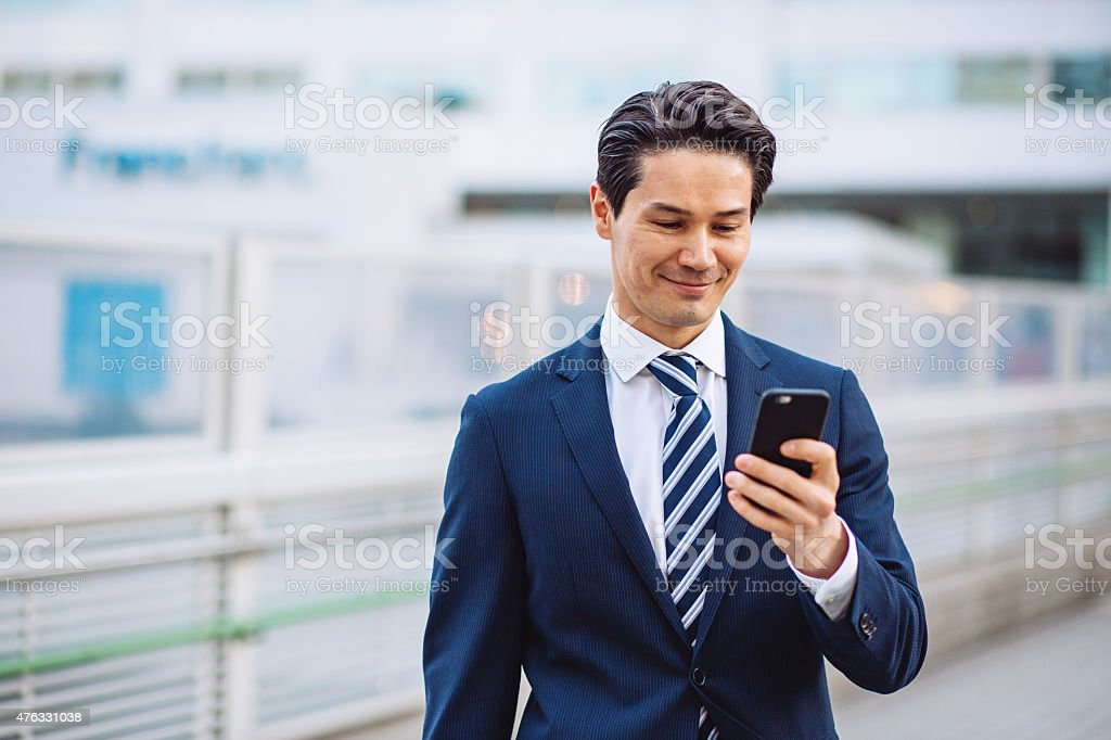 Japanese businessman in Tokyo with smart phone texting outdoors stock photo