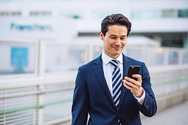 東京で日本のビジネスマン、スマートフォン、屋外でのリラクゼーション ストックフォト