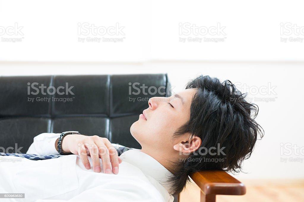 Japanese businessman lying down on a sofa foto royalty-free