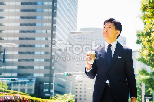 Japanese businessman on his way to work with coffee on a sunny morning. He is looking up, enjoying the sunshine. Photographed in Shijuku, Tokyo, Japan.
