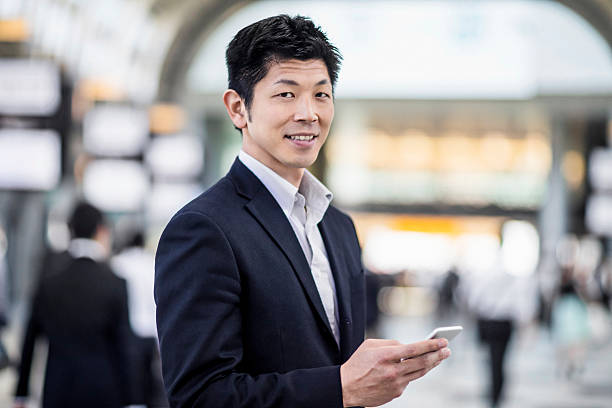 Japanese businessman portrait looking at his phone at the station stock photo