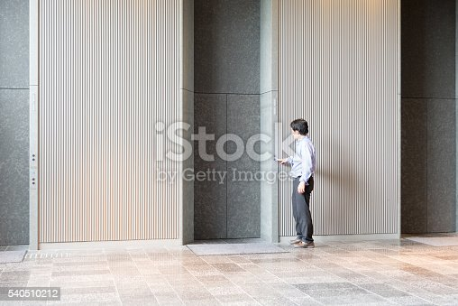 638591126 istock photo Japanese businessman standing and waiting for elevator 540510212
