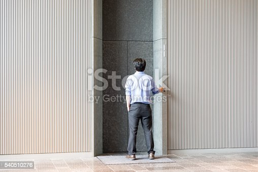 638591126 istock photo Japanese businessman standing and waiting for elevator 540510276