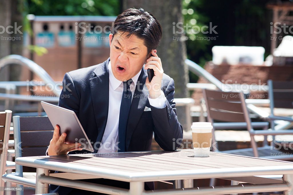 Japanese businessman swears on mobile phone while looking at tablet stock photo