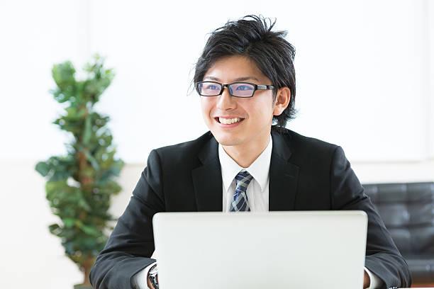 japanese businessman using a laptop - ビジネスマン ストックフォトと画像