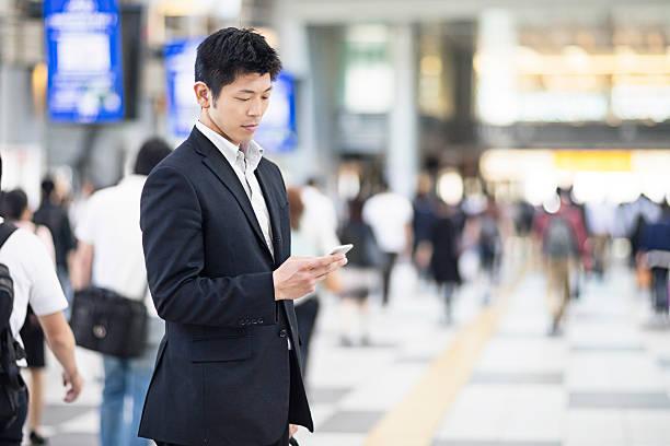駅で携帯電話を使った日本人ビジネスマン - メッセージ ストックフォトと画像
