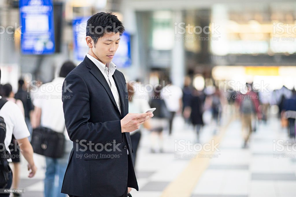 Japanese businessman using mobile phone at the station stock photo