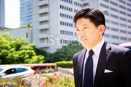 Japanese businessman walks to work with grim determination looking ahaead wit a tight lipped mouth. Photographed in Shinjuku, Tokyo, Japan.