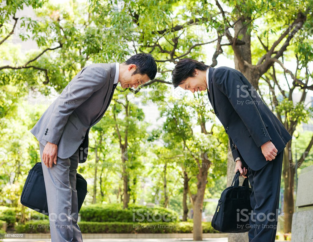 Japanese businessmen bowing to each other stock photo