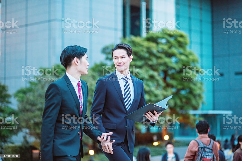 Japanese businessmen in Tokyo having a conversation outdoors stock photo