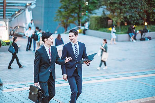 東京で日本のビジネスマンが、会話、屋外 - サラリーマン ストックフォトと画像