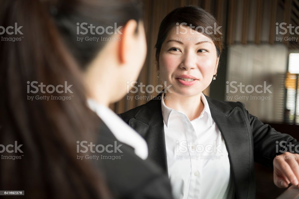 Japanese businesswoman listening to female colleague stock photo