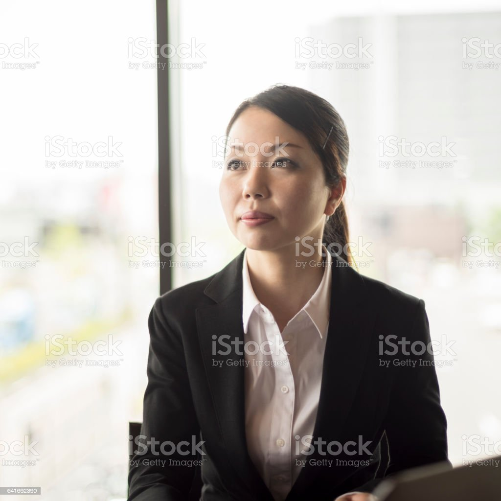 Japanese businesswoman looking away with pensive expression stock photo