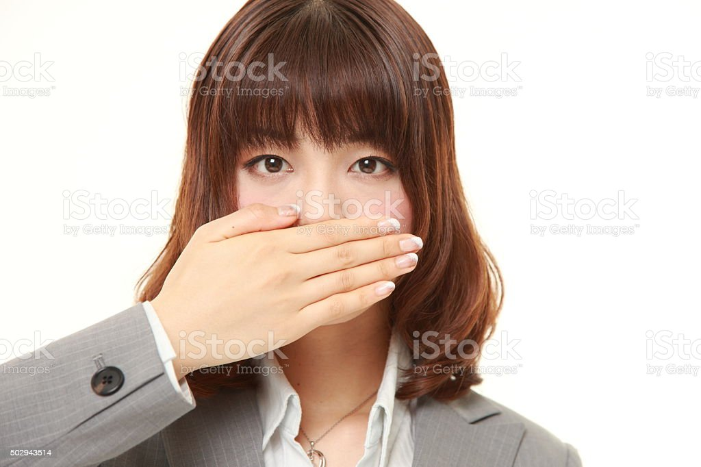 Japanese businesswoman making the speak no evil gesture stock photo