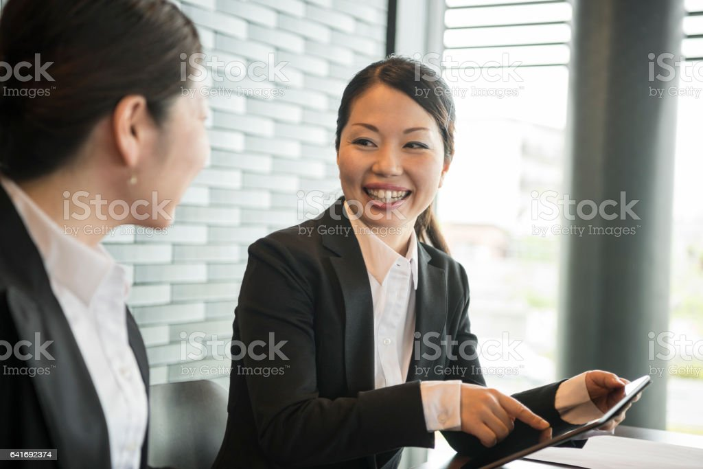 Japanese businesswoman smiling at colleague, candid portrait stock photo
