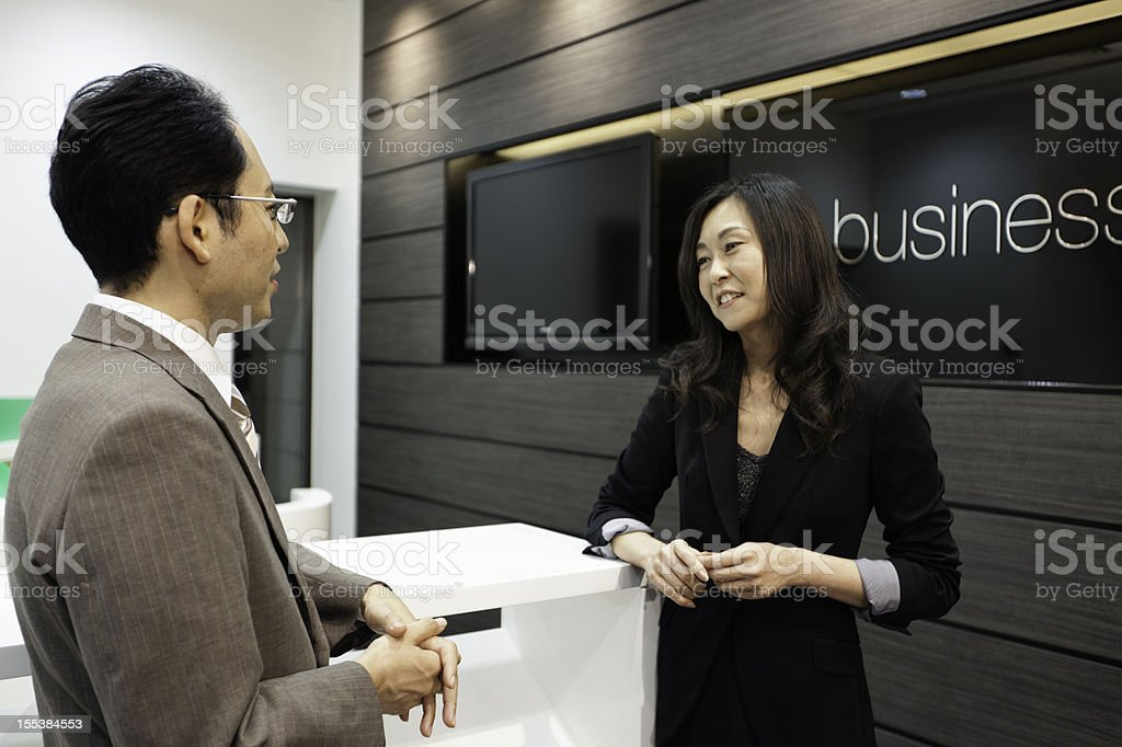 Japanese businesswoman talking to a  male coworker in business lounge. royalty-free stock photo