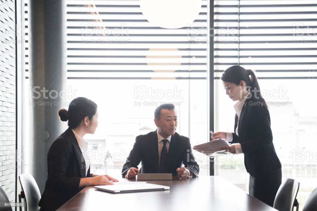 Japanese businesswoman talking to two colleagues in business meeting stock photo