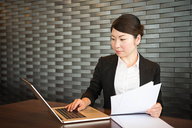 Japanese businesswoman using laptop in office - foto de stock