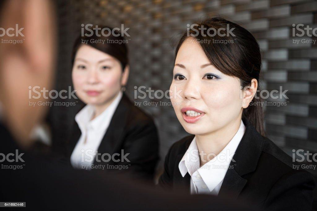 Japanese businesswomen listening to colleague stock photo