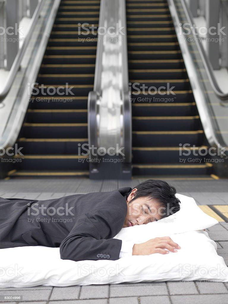 Uomo d'affari giapponese che dorme su futon, esterno foto stock royalty-free