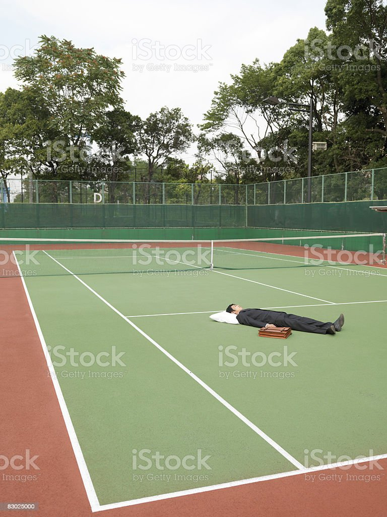 Japanese bussiness man sleeping on tennis court royaltyfri bildbanksbilder