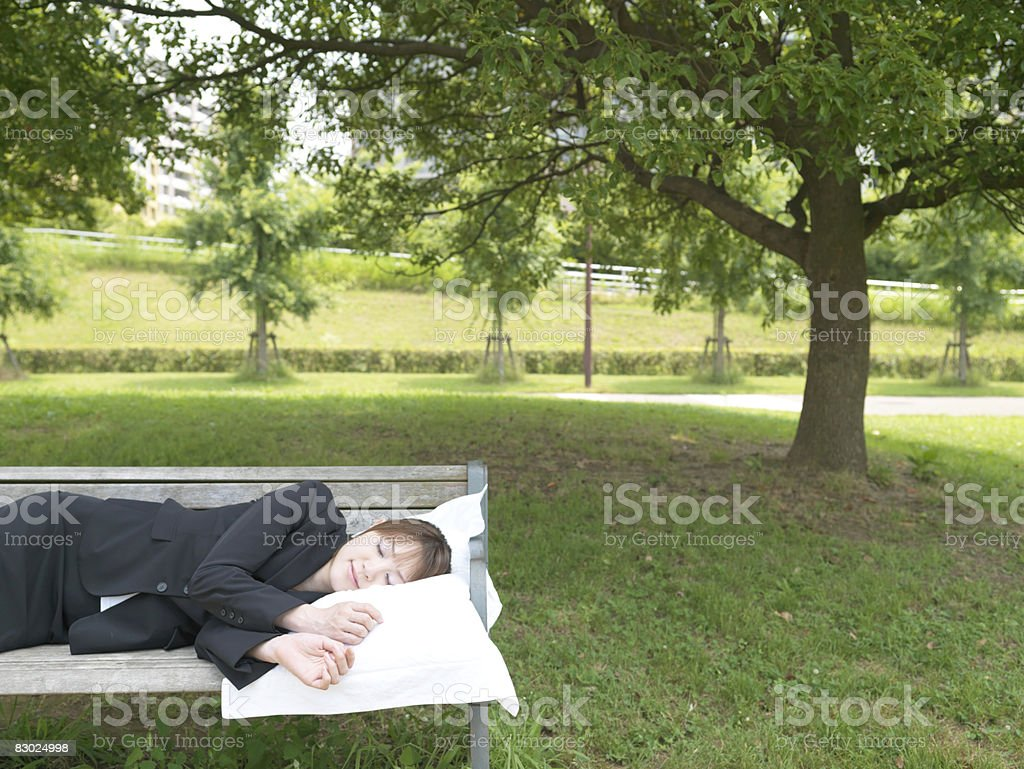 Japanese bussiness woman sleeping on the bench royalty free stockfoto