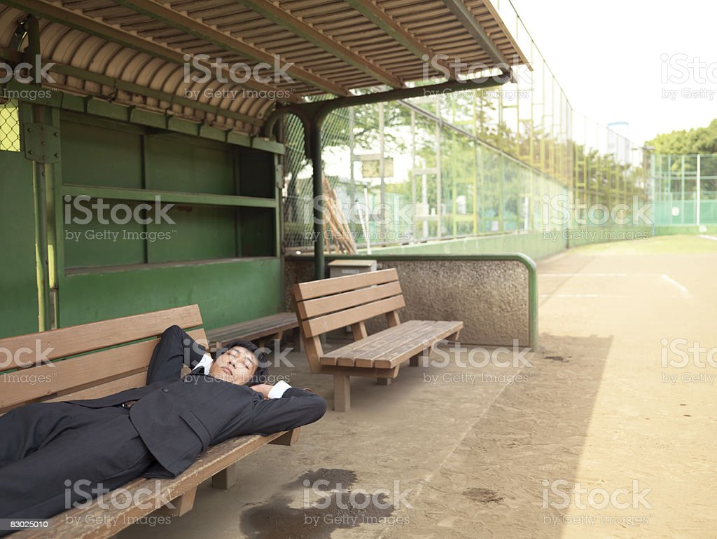 Giapponese bussinessman dormire a baseball park foto stock royalty-free