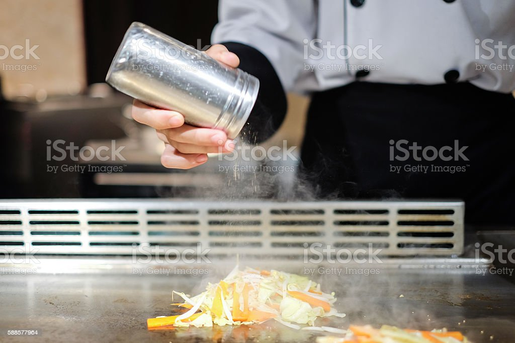 Japanese chef deliberately preparing and cooking traditional vegetables  beef teppanyaki stock photo