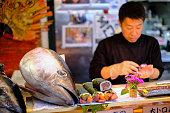 Japanese chef prepares fresh Japanese seafood sushi in Dontobori's famous fresh seafood Kuramon Ichiba market in Namba, Osaka, Japan.