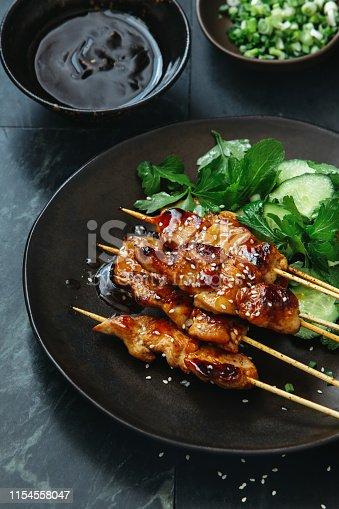 Japanese chicken yakitori skewers with vegetables salad on dark background