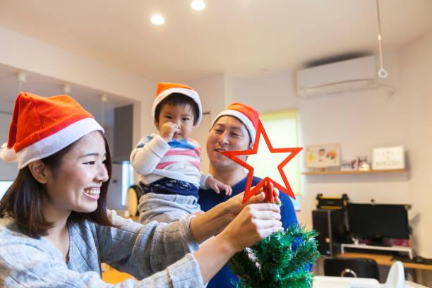 bambino giapponese con albero di natale - santa claus tiptoeing foto e immagini stock