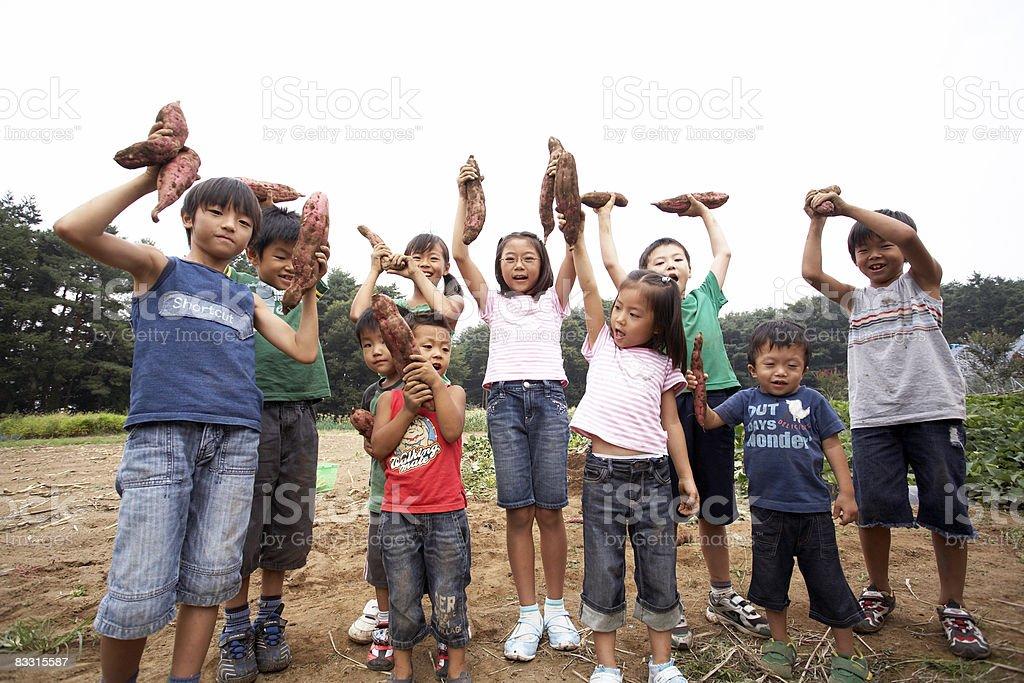 Japanese dzieci gospodarstwa Słodkie ziemniaki w powietrzu zbiór zdjęć royalty-free
