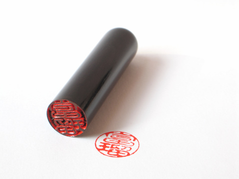 High quality, carved, black Japanese stamp (chop or hanko), laying on its side, showing detail of carving; isolated; focus on stamp and carved end.