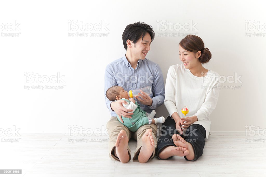 Japanese couple giving milk to baby stock photo