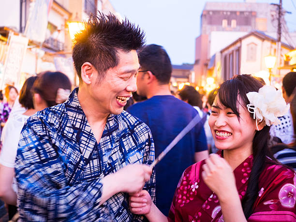Japanese couple laughing with joy on the street at festival stock photo