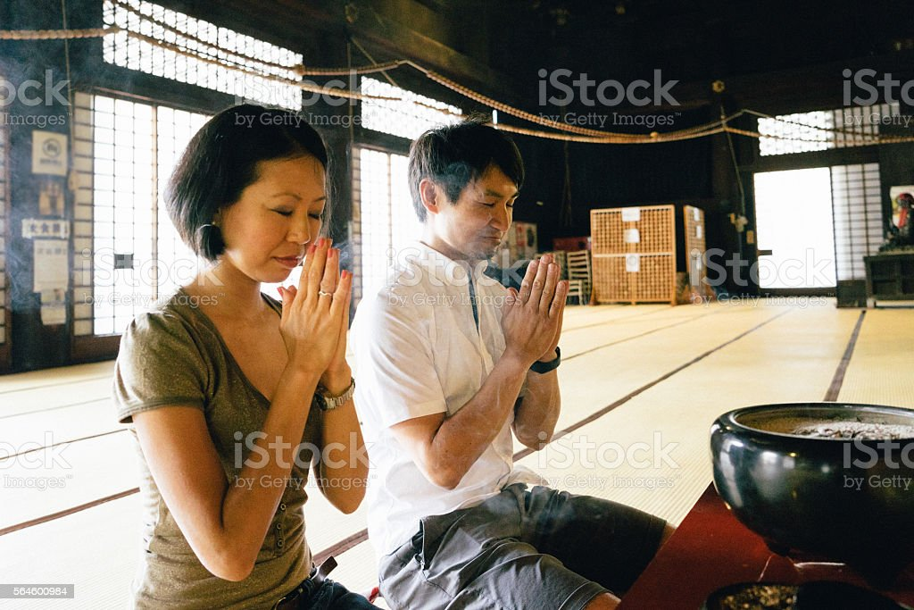 Japanese couple praying in a buddhist temple - foto de acervo