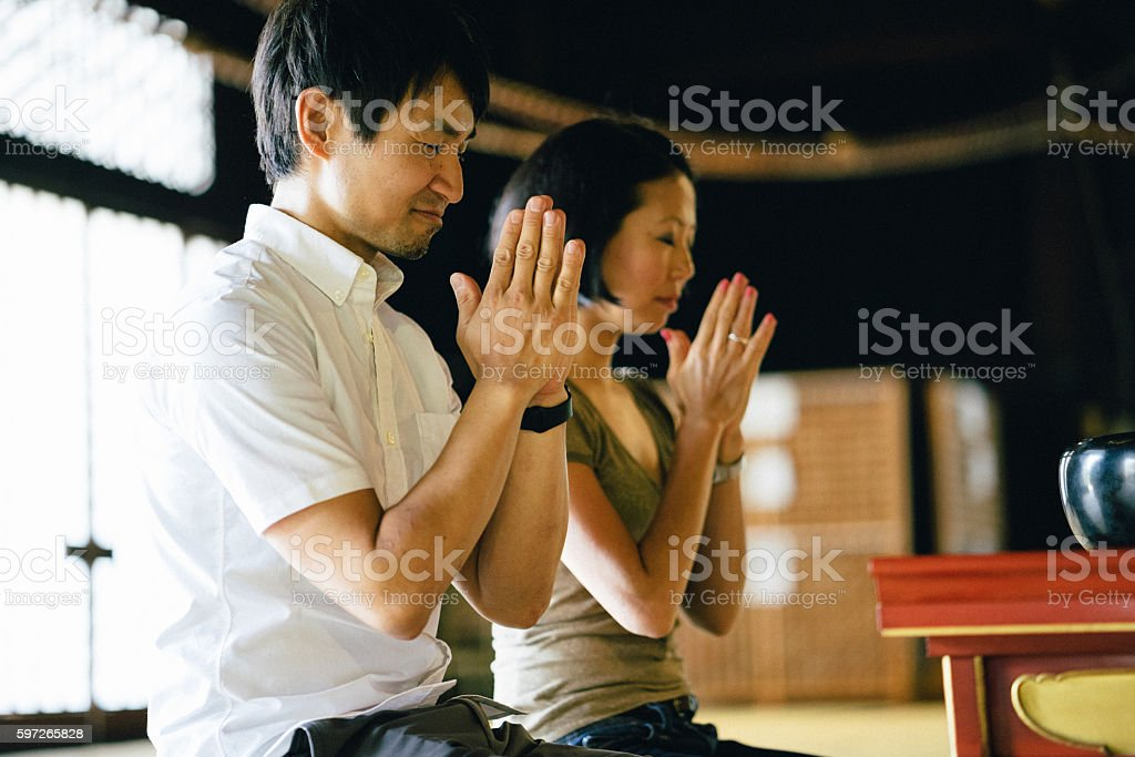 Japanese couple praying in a buddhist temple royalty-free stock photo