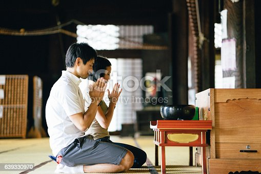 Japanese couple praying in a buddhist temple in Kyoto, Japan