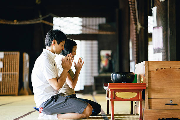 Japanese couple praying in a buddhist temple Japanese couple praying in a buddhist temple in Kyoto, Japan shrine stock pictures, royalty-free photos & images