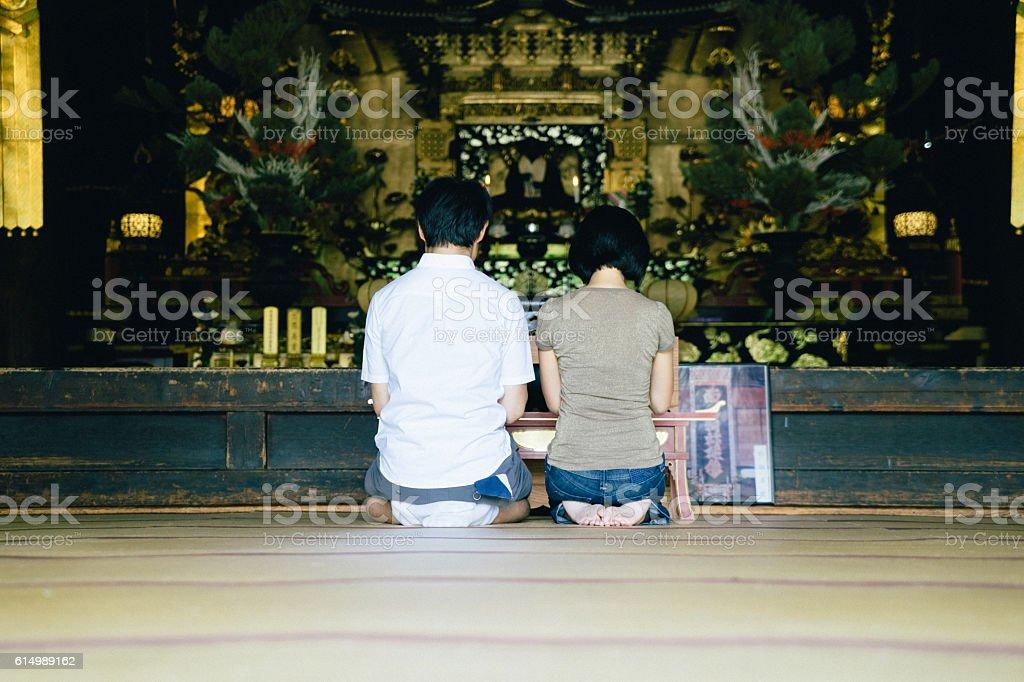 Casal japonês orar em um templo budista, Vista traseira - foto de acervo