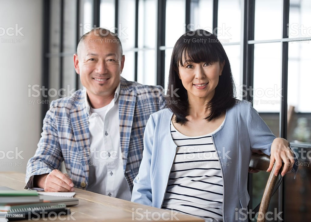 Japanese couple sitting at table stock photo
